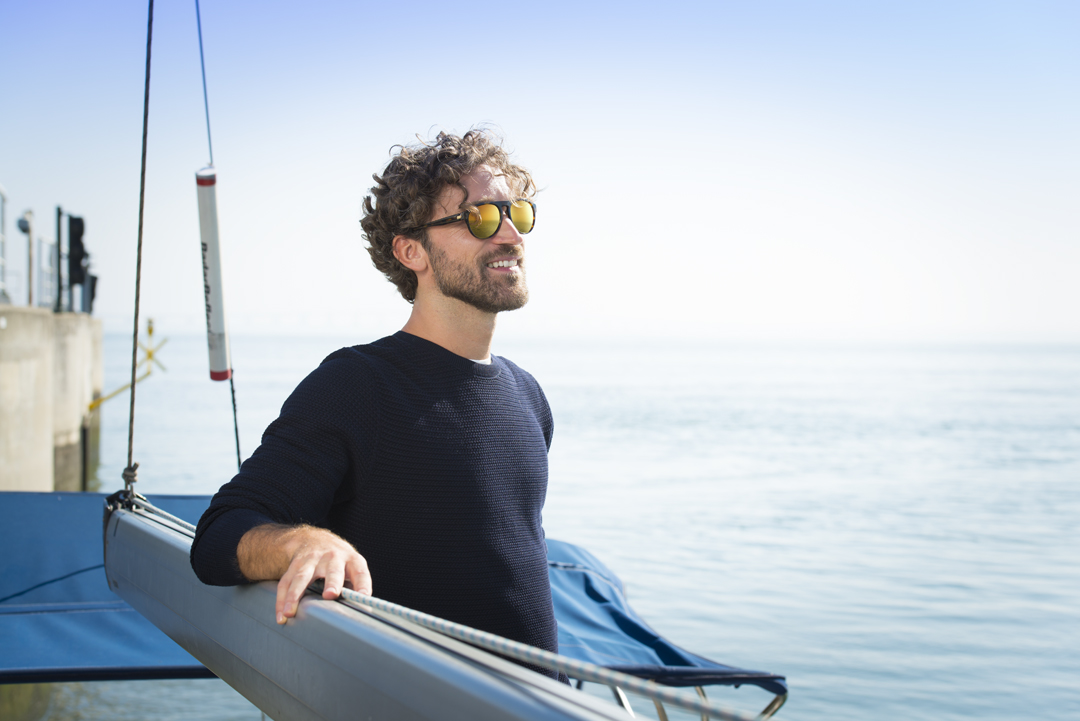 Man wearing E-Mirror UV lenses stood on a boat