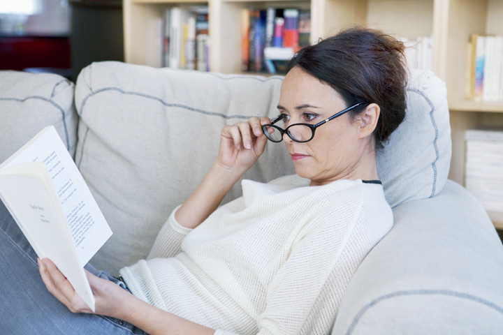 Woman wearing reading glasses struggling to see text on page