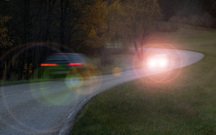 Cars driving at night with flared headlights