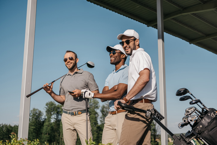 Three men wearing sunglasses playing golf