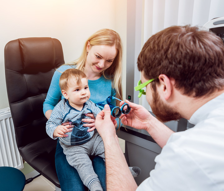 Little boy sat on mother's lap having an eye examination