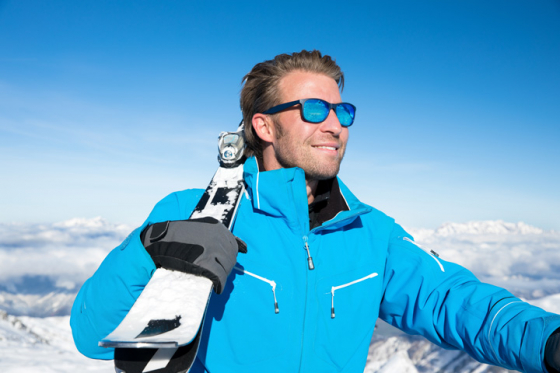 Man holding skis looking into the distance through his polarised UV protective sunglasses