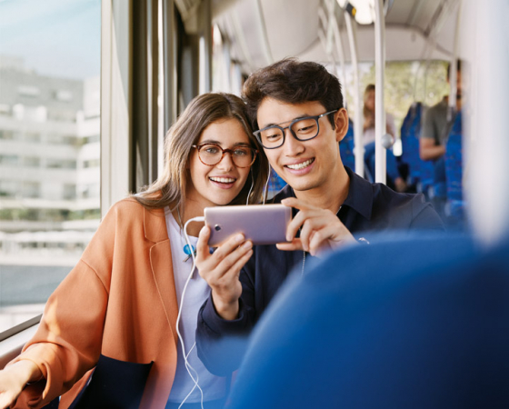 Woman and man sat on bus looking at smartphone