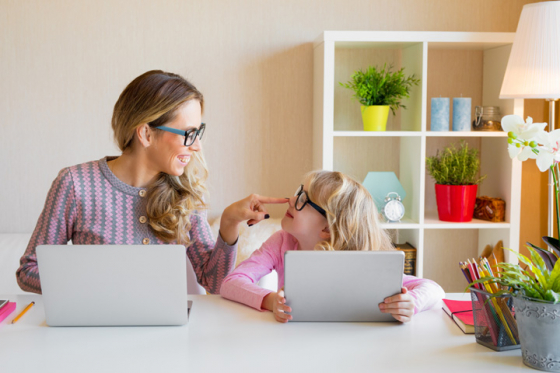 Mother and daughter wearing glasses looking at laptop