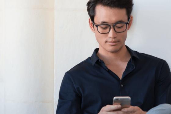 man looking at his phone wearing eyezen lenses