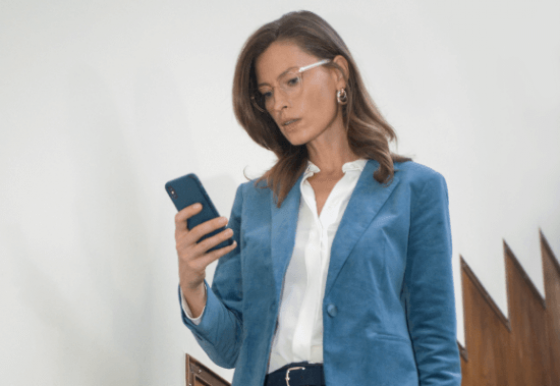 woman looking at her phone wearing varifocals