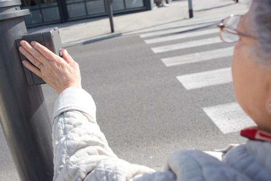 Woman wearing glasses waits to cross road