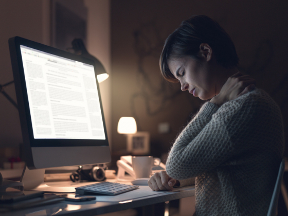 Woman holding neck in pain whilst working on bright computer screen