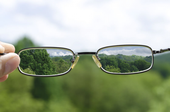 glasses being held up to a landscape showing correction through the lenses