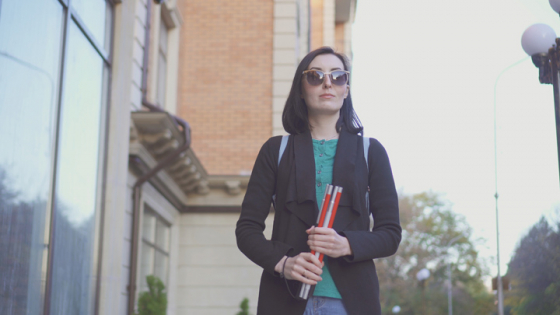 Woman with visual impairment walking along the street with cane