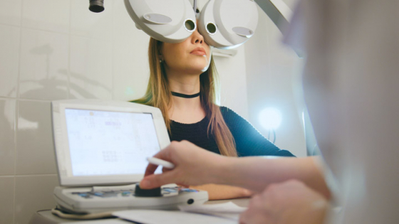 A woman having a full eye examination with an phoropter head