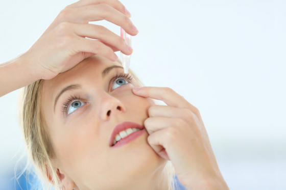 woman placing eye drops in her eye to cure dry eye