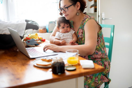 Mum multi-tasking, holding baby while working on laptop