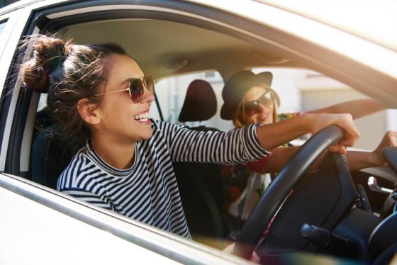 Two women wearing sunglasses driving