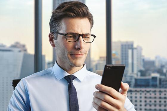 Man wering Varilux X series lenses checking message on smart phone