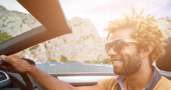 Man driving a convertible car wearing sunglasses