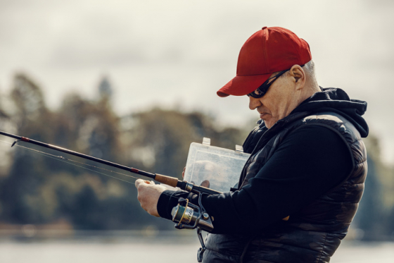Man wearing sunglasses tying hook on fishing line
