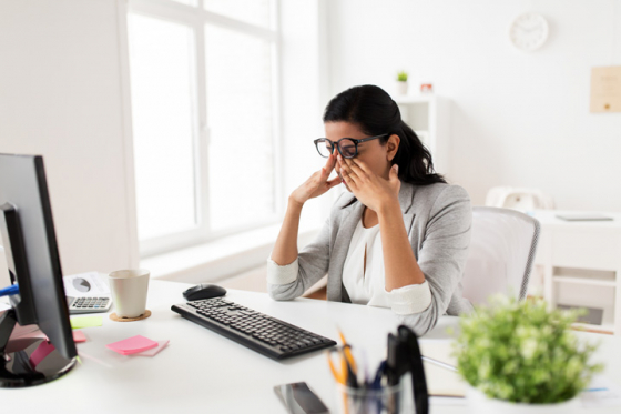 Woman suffering from eyestrain whilst working on her computer
