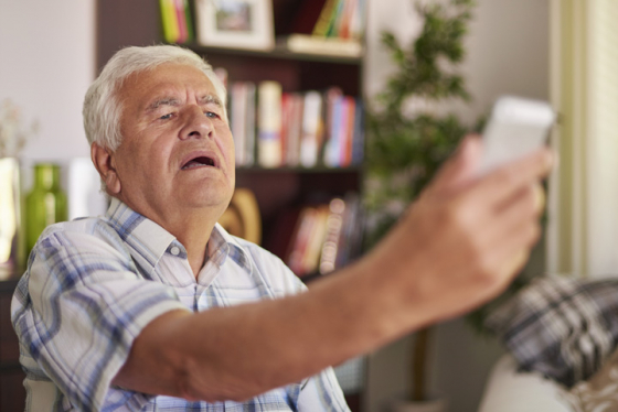 Man struggling to see the text on his phone due to presbyopia
