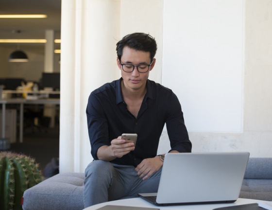 Man looking at smartphone wearing Eyezen lenses