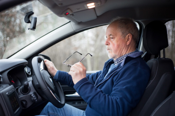 Man driving with glasses in his hands